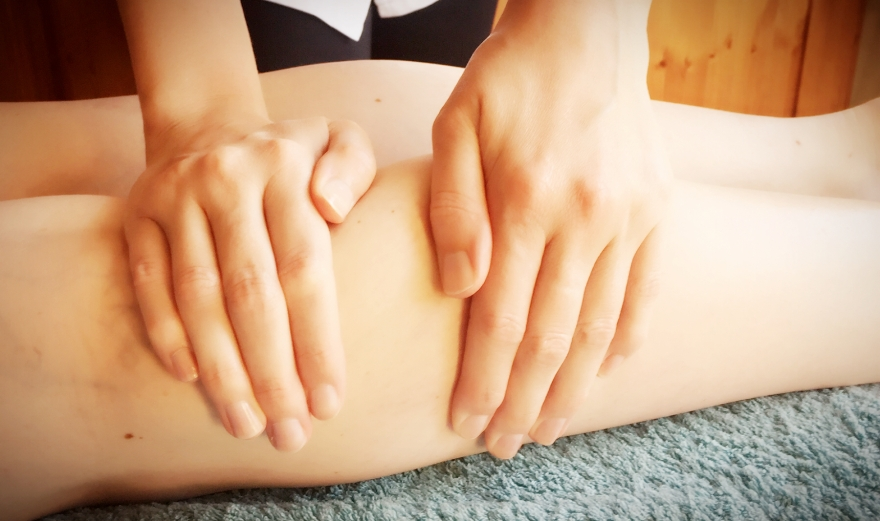Image of two hands giving a sports massage on the legs
