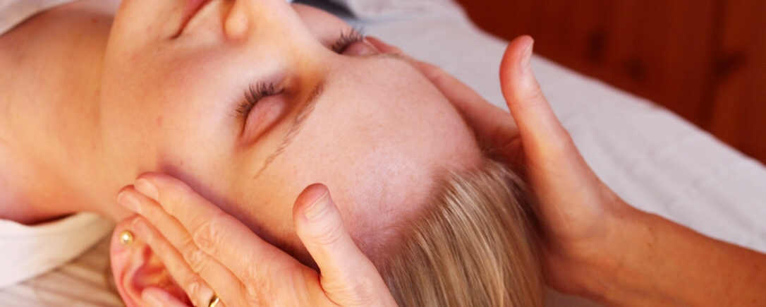 Image of a female lying down receiving osteopathy treatment to the head and neck