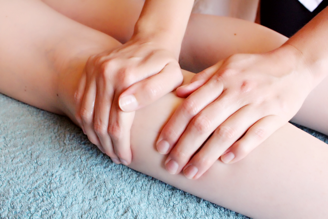 Image of two hands giving a sports massage on the calf