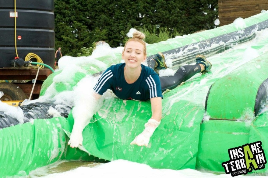 Picture of a female runner sliding down a water slide head first as part of a muddy run race